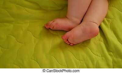 little feet a newborn baby on green blanket
