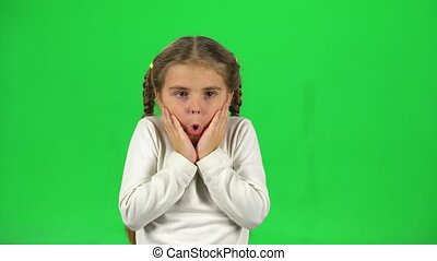 Little female is surprised and scared in studio on green screen.