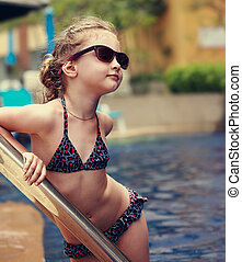 Little female model posing in fashion kids sunglasses and swimsuit near swimming pool