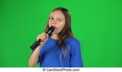 Little female singing into microphone on green screen at studio