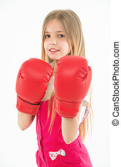 Little fighter before combat. Girl with long blond hair wearing huge red boxing gloves, sport concept. Kid in pink overalls isolated on white background. Brave girl ready to protect herself