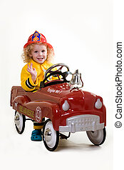 Portrait of an adorable little three year old boy wearing fireman costume sitting in a toy firetruck over white