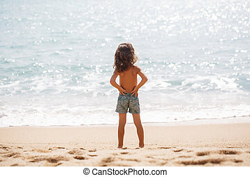 Little five years old boy is watching on the sea