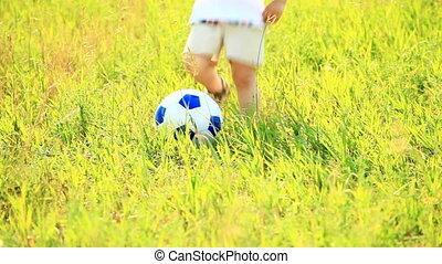 Little football player kicks the ba