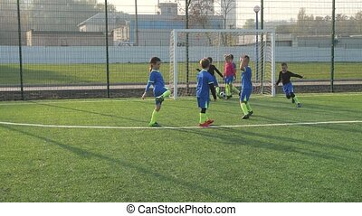 Skillful preadolescent footballer successfully hitting penalty and scoring goal while playing soccer match on football field. Happy preteen soccer players rejoicing at masterfully scored penalty shot