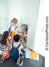 Little frightened girl sitting in the school locker having mockery at school