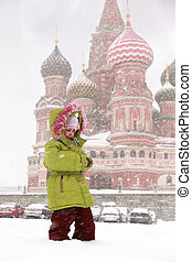 Little frozen girl standing in front of St. Basil's Cathedral in Moscow, Russia at wintertime during snowfall