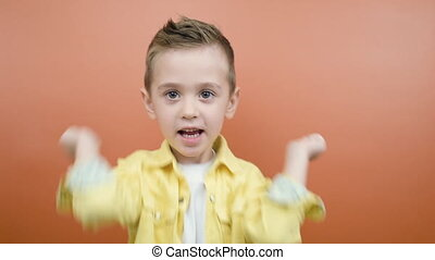 Little fun happy kid boy 4-5 years old in yellow shirt posing clenching fists doing winner gesture say Yes isolated on orange background studio