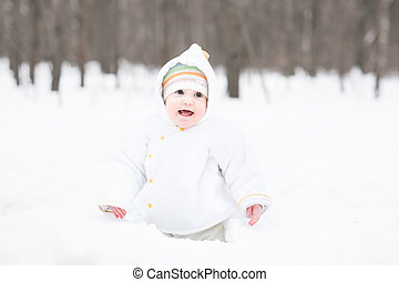 Little funny baby digging in the snow