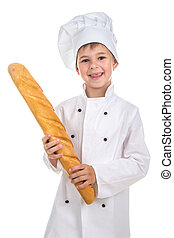 Little funny boy dressed in chef uniform with fresh baguette.