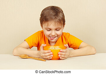 Little funny boy is going to eat cereal