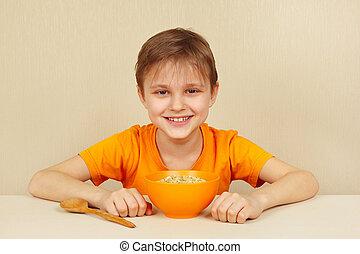 Little funny boy is going to eat porridge
