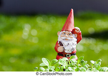 Little funny garden gnome is standing outside