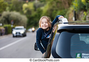 Little funny girl grimaces, leaning out of the car window. Family travel by car in Europe.