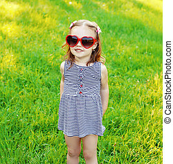 Little funny girl in sunglasses on the grass summer