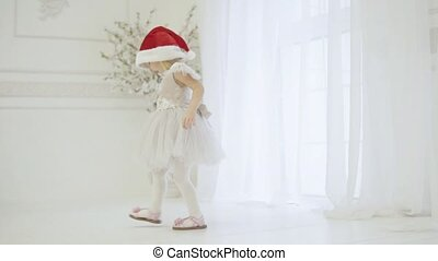 Little funny girl is waiting for a meeting with Santa Claus