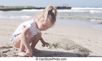 Little funny girl playing on the beach near the sea