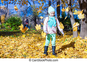 Little funny girl throws autumn leaves in park on fall day -...
