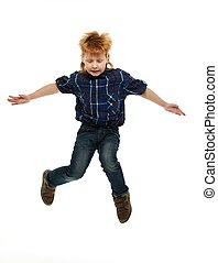 Little funny redhead boy in shirt and jeans jumping