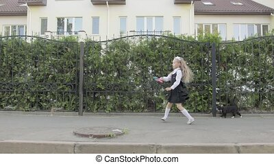 Little funny schoolgirl in school uniform and briefcase on his shoulders walking around the area. In the hands of the girl rainbow spinner, near the road is a cat