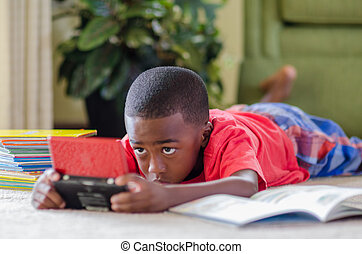 Little Gamer - A young African American boy laying on the...