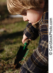 A young boy digs in the garden with a hand shovel