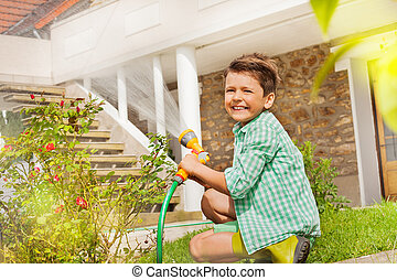 Little gardener watering plants at the backyard - Portrait...