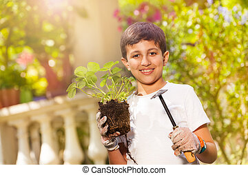 Little gardener with strawberry plants and trowel