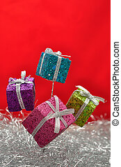 Little gifts in shinny wrapping for decorating a Christmas tree with silver tinsel and a red background