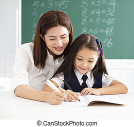 little gile in class writing with teacher helping