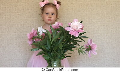 Little girl 2 years admiring the bouquet of peonies....