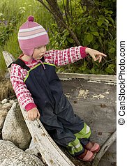 Little girl (3 years old) playing in an old wooden boat, pointing the direction.