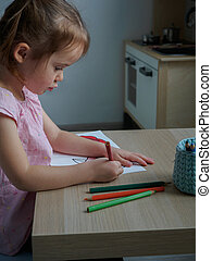 Little girl 4 years old painstakingly draws in her coloring book at a wooden table in her room