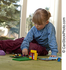 Little girl (4 years old) playing with regular sized building bricks.