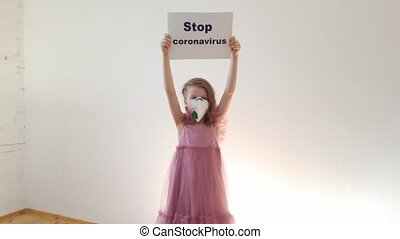 Little girl 7 years old in a medical mask shows banner Stop ...