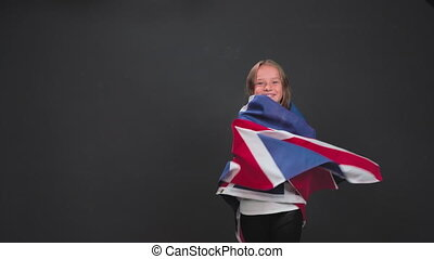 Little girl 8 -10 years old dancing twirling in the studio wrapped in UK or British flag isolated on dark gray or black background. High quality footage.
