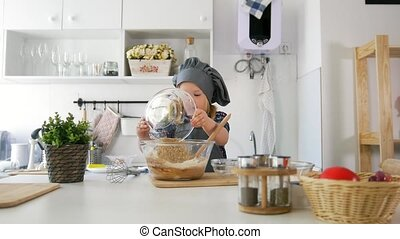Little girl adds ingredients to the pastry dough