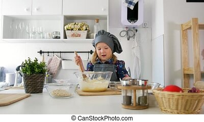 Little girl adds oatmeal to the pastry dough