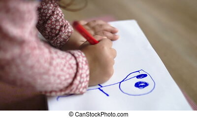 Little girl drawing cute blue and red figures on white paper box. Young child doodling on paper with red pencil. Kids doing arts and crafts
