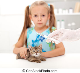 Little girl afraid for her kitten getting a vaccine at the veterinary - focus on syringe