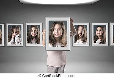 Little girl among lots of her portraits