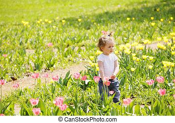 Little girl among tulips
