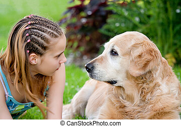 Little girl and a dog in an outdoor setting