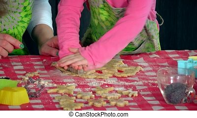 Little girl and adult woman hands making cookies with metallic forms