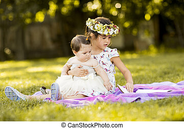 Little girl and baby sitting in the grass
