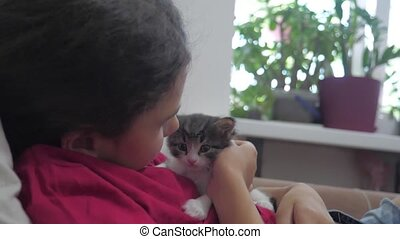 little girl and black and white fluffy kitten lie on the bed. girl stroking a small kitten slow motion lifestyle video. girl and kitten concept