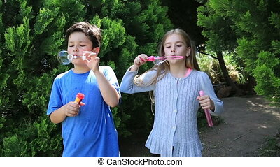 Little girl and boy  blowing a soap