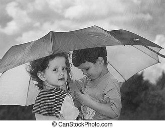 little girl and boy hiding under an umbrella from the rain,...