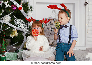 Little girl and boy in reindeer antlers eating a lollipops
