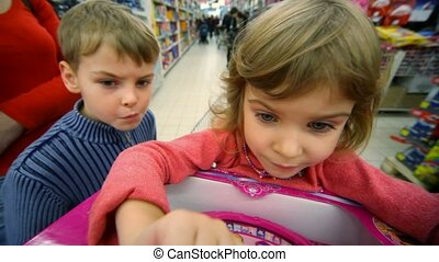 little girl and boy playing logic game in mall